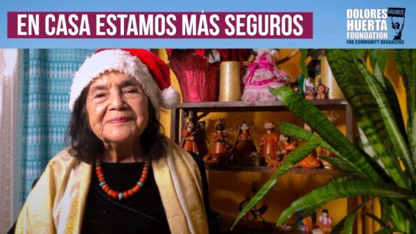 Dolores Huerta wearing a Santa Cap with the words En Casa Estamos Mas Seguros